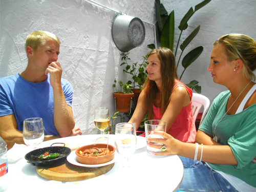 three students of Spanish tasting tapas with school