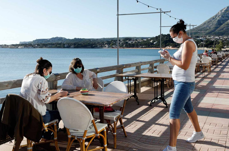 People in a terrace in Denia wearing masks