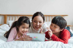 Madre con i suoi due figli che usano un'app per imparare lo spagnolo